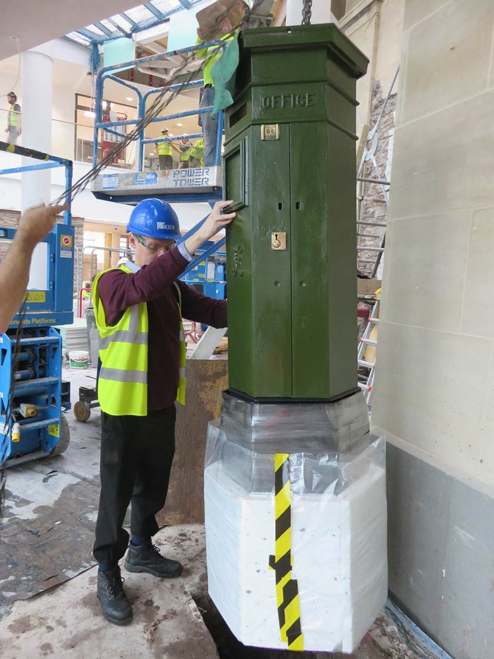 Nigel-Blackamore-the-Senior-Curator,-assists-with-the-installation-of-the-restored-Penfold-pillar-box